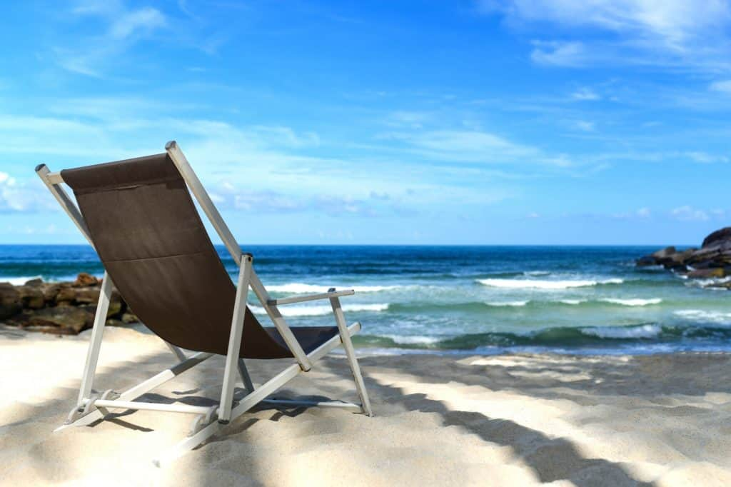 Chair place on tropical beach for background.