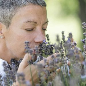 Wellbeing in Nature. Woman Enjoying the Scent of Lavender Flowers